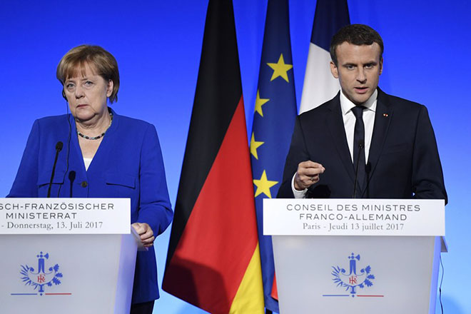 epa06084971 German Chancellor Angela Merkel (L) and French President Emmanuel Macron (R) speak at a joint news conference at the Elysee Palace in Paris, 13 July 2017. The French-German Ministerial Council was meeting earlier the same day in Paris.  EPA/JULIEN DE ROSA