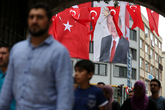epa06087042 People walks in front of a huge Turkish flag and Turkish President Recep Tayyip Erdogan's picture in Istanbul, Turkey, 14 July 2017. The 15 July 2017 event marks the first anniversary of the failed coup attempt which led to some 50 thousand workers being dismissed, some eight thousand people arrested, and scores of news outlets shut down by the government. Turkish President Recep Tayyip Erdogan blamed US-based Turkish cleric Fetullah Gulen and his movement for masterminding the failed coup and Turkey remains under a state of emergency as a result.  EPA/ERDEM SAHIN