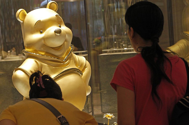 epa02888861 A giant pure gold statue of the Disney character Winnie the Pooh is on display at a shopping mall in Hong Kong, China, 30 August 2011. Standing at approximately 113cm high, and weighing a total of 17kg, it is claimed by Hong Kong jewelry chain Chow Tai Fook that the statue is the tallest gold 'Winnie the Pooh' statue in the world. It is unclear how many gold  'Winnie the Pooh' statues there are around the world.  EPA/ALEX HOFFORD