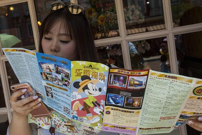 epa05993614 A mainland Chinese tourist consults a map of Hong Kong Disneyland, in Hong Kong, China, 27 May 2017. The numbers of tourists visiting Hong Kong Disneyland has declined since Shanghai Disneyland opened in June 2016. Shanghai Disney Resort has announced on 19 May that more than 10 million people have visited the park after eleven months of operations, outshining its Hong Kong counterpart which has posted financial losses for two consecutive years.  EPA/ALEX HOFFORD