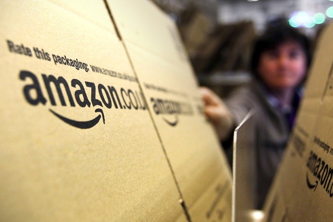 An employee selects a branded cardboard box at the Amazon.co.uk. Marston Gate 'Fulfillment Center,' the U.K. site of Amazon.com Inc., in Ridgmont, U.K., on Monday, Dec. 5, 2011. Amazon.com Inc.'s share of the tablet computer market will surge to 14 percent this quarter as consumer demand catapults the Kindle Fire to the No. 2 spot after Apple Inc.'s iPad, according to research firm IHS Inc. Photographer: Chris Ratcliffe/Bloomberg via Getty Images