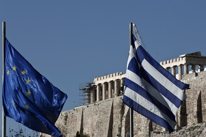 A Greek (R) and an EU flag flutter in front of the temple of the Parthenon, during the takeover ceremony of the six-month rotation of Greece's EU Presidency at Zappeion Hall, in Athens January 8, 2014. REUTERS/Yorgos Karahalis   (GREECE - Tags: POLITICS) - RTX1768O