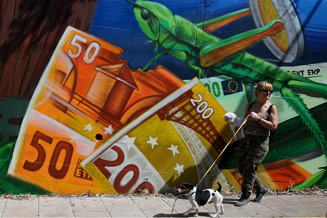 epaselect epa05941858 A woman walks past graffiti depicting euro banknotes, in Athens, Greece, 03 May 2017. Greece has reached a preliminary bailout deal with its international creditors.  EPA/ORESTIS PANAGIOTOU