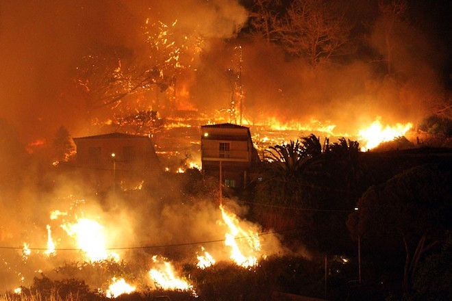 Forest fires rage near houses on the hills above the city of Funchal in the Portuguese Atlantic island of Madeira Wednesday night, July 18, 2012. Residents living near wooded areas at the edge of the island's largest city fled in panic after one blaze engulfed an unspecified number of houses and threatened others. (AP Photo/Joana Sousa)