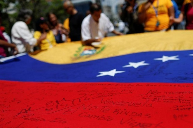 "A message written on a Venezuelan national flag that reads, ""Venezuela don't give up"", is seen during a gathering to demand a referendum to remove President Nicolas Maduro in Caracas, Venezuela, June 6, 2016. REUTERS/Carlos Garcia Rawlins"