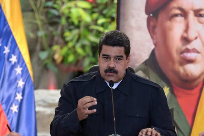 Venezuela's President Nicolas Maduro speaks in front of an image of Venezuela's late President Hugo Chavez, during a meeting with ministers in Caracas, Venezuela January 10, 2017. Miraflores Palace/Handout via REUTERS     ATTENTION EDITORS - THIS PICTURE WAS PROVIDED BY A THIRD PARTY. EDITORIAL USE ONLY. - RTX2YCMX