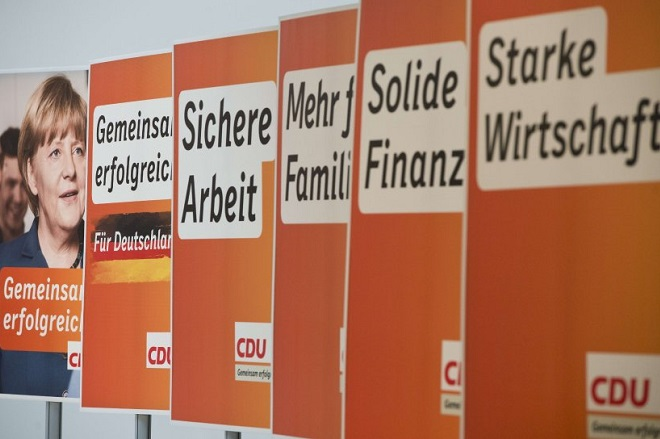 "Election campaign placards for the Christian Democratic Party (CDU), featuring German Chancellor Angela Merkel (L), are presented at the CDU headquarters in Berlin, Germany on August 5, 2013. Germany goes to the polls in parliamentary elections on September 22, 2013. Slogans (R-L) read ""Strong Economy"", ""Sturdy Finances"", ""More for Families"", ""Job Security"" and ""Successfull Together"". AFP PHOTO / JOHN MACDOUGALL"