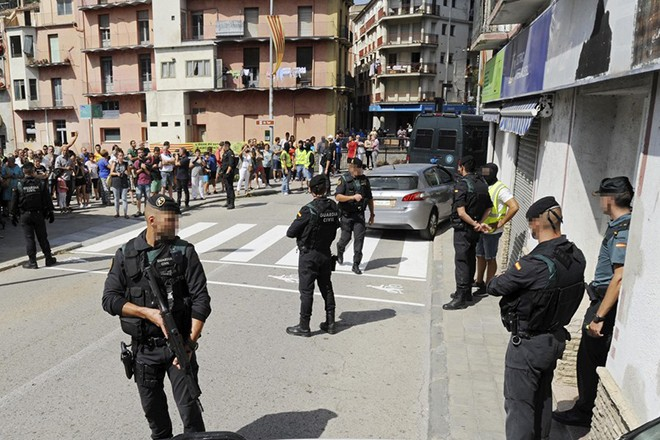 epa06149861 Spanish security forces members stand guard outside an appartment building during a raid in the town of Ripoll, Catalonia, Spain, 18 August 2017. Security forces arrested a 30-years-old man for his alleged involvement in Barcelona terrorist attack, who is a friend of the man arrested on 17 August in the same city, according to investigation sources. According to media reports, at least 14 people were killed and some 130 others injured after a van and a vehicle crashed into pedestrians in Las Ramblas in Barcelona and in a promenade in Cambril. Police have stated that the attack in Barcelona and the attack in Cambrils were linked. The so-called 'Islamic State' (IS) has claimed responsibility for the attack in Barcelona.  EPA/ROBIN TOWNSEND