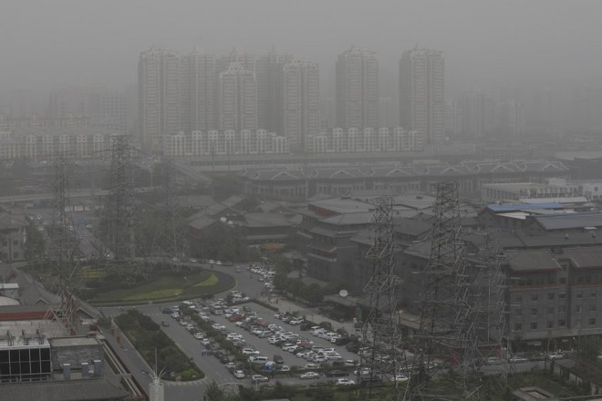 epaselect epa05942935 A general view shows buildings seen through a heavy sandstorm hitting Beijing, China, 04 May 2017. The Beijing and national meteorological authorities issued a blue alert on air pollution as a sand storm hit the region.  EPA/WU HONG