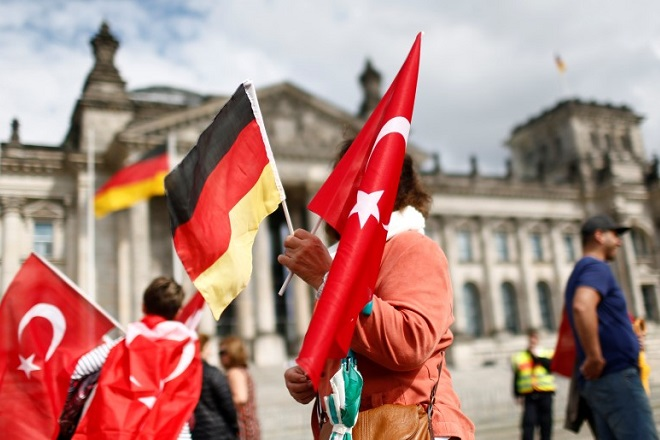 Demonstrators hold Turkish and German flags in front of the Reichstag, the seat of the lower house of parliament Bundestag in Berlin, Germany, June 1, 2016, as they protest against a disputed vote in Germany's parliament on Thursday, on a resolution that labels the killings of up to 1.5 million Armenians by Ottoman forces as genocide.  REUTERS/Hannibal Hanschke