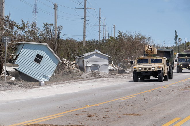 epa06201181 A US National Guard disaster relief convoy traverses past storm surge debris on the Overseas Highway (US 1) after Hurricane Irma struck the Florida Keys in Marathon, Florida, USA, 12 September 2017. Many areas that sustained damage during the storm remain under a dawn to dusk curfew.  EPA/ERIK S. LESSER