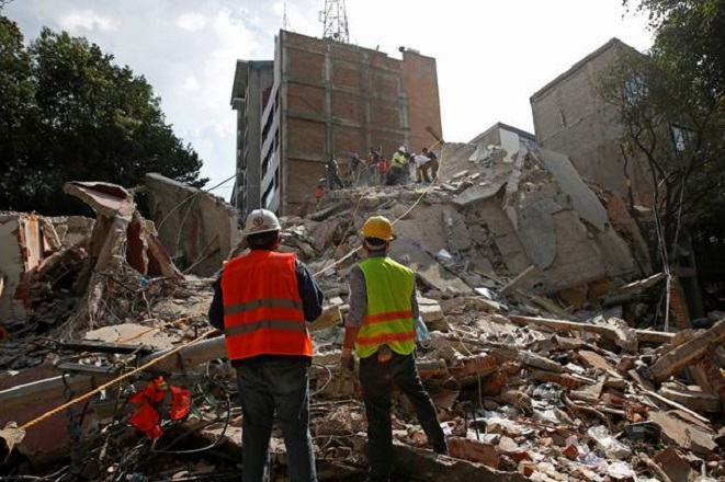Rescue workers look at fellow workers searching for people under the rubble of a collapsed building after an earthquake hit Mexico City, Mexico September 19, 2017. REUTERS/Carlos Jasso