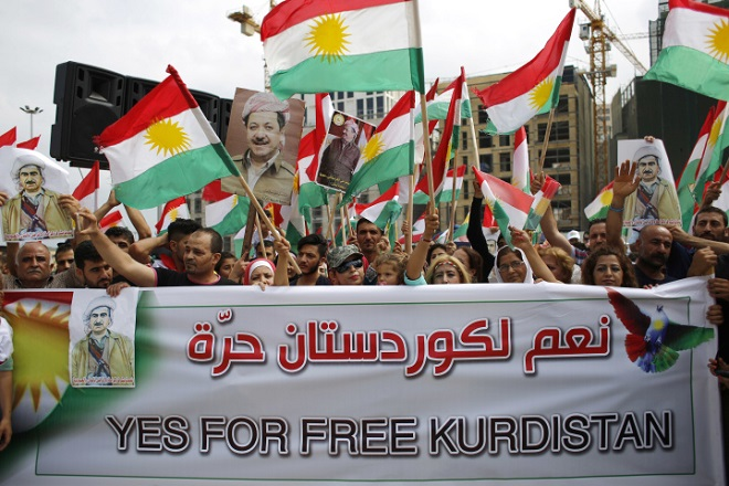 File - In this Sunday, Sept. 17, 2017 file photo, Kurds wave Kurdish flags during a rally to support an independence referendum in Iraq, at Martyrs Square in Downtown Beirut, Lebanon. On Monday Sept. 18, 2017, Iraq's Supreme Court issued a temporary ban on a Kurdish autonomous region's referendum on independence scheduled for Sept. 25. (AP Photo/Hassan Ammar)