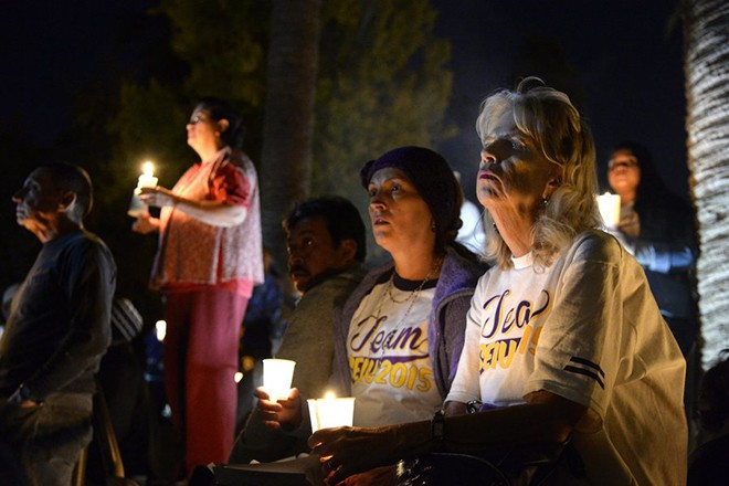 epa05058949 People hold candles during a candlelight vigil for the mass shooting victims in downtown San Bernardino, California, USA, 07 December 2015. Assailants Syed Farook and his wife, in what authorities are now calling 'an act of terror', killed 14 people and injured 21 other before they died in a shoot-out with police 02 December 2015.  EPA/MIKE NELSON