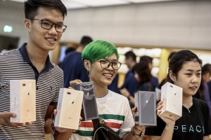 epa06218681 Customers hold up newly purchased iPhone 8 units at the Apple Orchard store in Singapore, 22 September 2017. The iPhone 8, iPhone 8 Plus and iPhone X were announced by tech giant Apple as the latest iterations of their iconic mobile devices.  EPA/WALLACE WOON