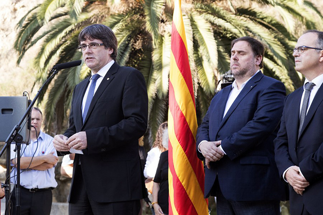 epa06267028 Catalonian regional President Carles Puigdemont (L) delivers a speech next to regional Deputy President Oriol Junqueras (2-R) and regional Presidency Minister Jordi Turull (R) during the traditional floral tribute at the grave of late Catalonian regional president Lluis Companys to mark the 77th anniversary of his death in Barcelona, Spain, 15 October 2017. Companys was executed by Francisco Franco's forces on 15 October 1940.  EPA/MARTA PEREZ