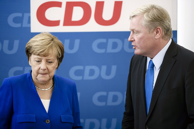 epaselect epa06268886 German Chancellor Angela Merkel (L) of the Christian Democratic Union (CDU) stands next to Bernd Althusmann (R), leader of the Christian Democratic Union (CDU) in Lower Saxony and top candidate for the state elections of his party, after he received flowers from her during a party's board meeting at the CDU headquarters in Berlin, Germany, 16 October 2017. According to preliminary official results, the CDU won 33.6 percent of the vote in Lower Saxony in the previous day's federal state elections, which were originally planned for 14 January 2018. The electoral term was brought forward after a deputy of the governing coalition had moved to the opposition fraction of conservatives, and the state government lost its one-vote majority in parliament.  EPA/CLEMENS BILAN