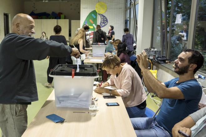 epa06239008 A Catalonian election official takes a photograph of a man voting in the closing hour  at a polling station for the '1-O Referendum' independence referendum in Barcelona, Spain, 01 October 2017. Spanish National Police officers and Civil guards have been deployed to prevent the people from entering to the polling centers to vote in the Catalan independence referendum, that has been banned by the Spanish Constitutional Court, but many people have managed to do it. The police action has provoked clashes between pro-independence people and the police forces.  EPA/JIM HOLLANDER