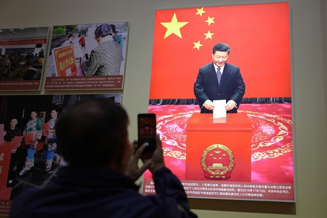 epa06285269 (FILE) - A visitor views a photograph of Chinese President Xi Jinping voting during an exhibition showcasing China's achievements over the past five years at the Beijing Exhibition Hall in Beijing, China, 28 September 2017 (reissued 24 October 2017). According to media reports on 24 October 2017, the National Congress of the Communist Party of China voted to enshrine the signature ideology of President Xi Jinping into the Chinese Communist Party constitution, elevating him to the country's most influential and powerful leader in decades. President Xi Jinping was also granted another five years in power during 19th Congress of the Communist Party of China.  EPA/WU HONG