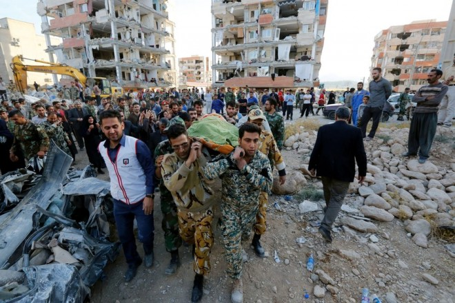 epa06326822 Iranian soldiers carry the body of an earthquake victim near the wreckage of a collapsed building in the city of Pole-Zahab, in Kermanshah Province, Iran, 13 November 2017. A 7.2 magnitude earthquake that struck Iran's Kermanshah province bordering Iraq has killed over 328 inhabitants and left at least another 3,950 injured, Iranian authorities said.  EPA/ABEDIN TAHERKENAREH