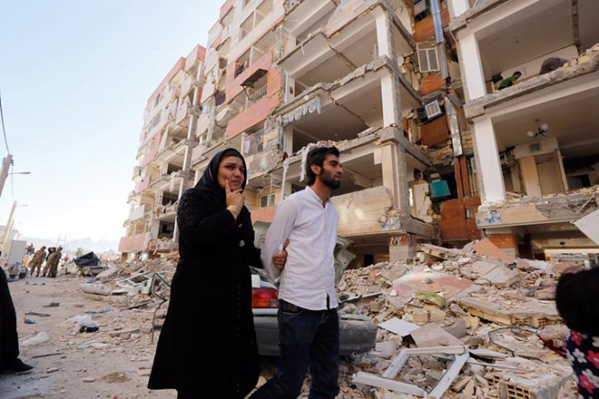 epa06328029 Iranian people walk near collapsed buildings at the earthquake site in the city of Sare Pole-Zahab in Kermanshah Province, Iran, 14 November 2017. A powerful 7.2 magnitude earthquake that struck Iran's Kermanshah province bordering Iraq late 12 November 2017 has at least killed over 440 inhabitants and left at least another 3,950 injured, Iranian authorities said.  EPA/ABEDIN TAHERKENAREH