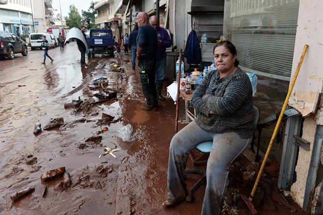 Γυναίκα σε απόγνωση απομακρύνει από το μαγαζί της τις λάσπες, στο κέντρο της Μάνδρας, Αττικής, Πέμπτη 16 Νοεμβρίου 2017, μετά τις καταρρακτώδεις βροχές που έπληξαν χθες την περιοχή. Τους 16 έχουν φτάσει οι νεκροί και πέντε ακόμα άνθρωποι αγνοούνται ενώ μεγάλες είναι οι καταστροφές σε σπίτια, καταστήματα και περιουσίες από τις χθεσινές πλημμύρες στη Μάνδρα, τα  Μέγαρα και τη Νέα Πέραμο στην Αττική. ΑΠΕ ΜΠΕ/ΑΠΕ ΜΠΕ/ΒΑΣΙΛΗΣ ΨΩΜΑΣ