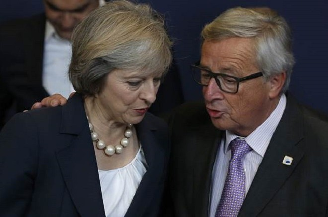 British Prime Minister Theresa May, left, and European Commission President Jean Claude Juncker talk during an EU summit group photo in Brussels on Thursday, Oct. 20, 2016. British Prime Minister Theresa May is set to hold her first talks with EU leaders and will tell them that the U.K.'s decision to leave the bloc is irreversible. (AP Photo/Alastair Grant)