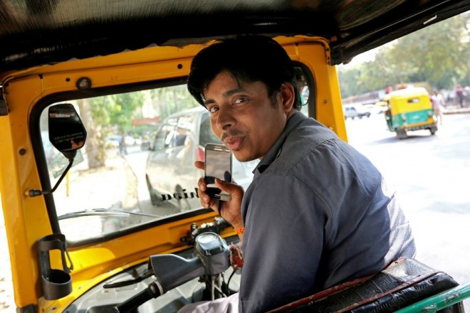epa04702943 Indian auto driver Sonu Chaudhary smiles as he gets a booking using the Uber app in New Delhi, India, 12 April 2015. Uber cab service provider has recently introduced a new online three wheeler booking service in Delhi through the uber mobile application. Commuters can avail the service without paying any booking charges and pay by cash for this service.The Uber is providing the cab service on a very discounted rates nearly as  the rates of  three-wheelers, but due to the wide availablity of three-wheelers in delhi, they have introduced this service.  EPA/HARISH TYAGI