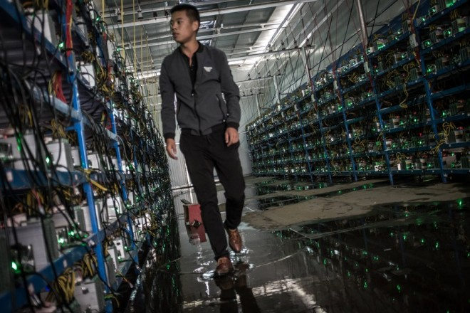 epa06062677 (06/26) Tibetan Bitcoin mine manager Kun walks in between aisles of mining machines in a Bitcoin mine in Sichuan Province, China, 26 September 2016. Kun is the mine's manager as well as one of its investors. He learned about Bitcoin through a friend and started investing in 2015. China, the world's leader in Bitcoin mining, is dominating both the currency's generation and the global trade in the currency. Sichuan has become known as 'the capital of bitcoin mining' as entrepreneurial Chinese set up 'mines' there due to its abundance of hydropower, perfect for the high electricity needs of the large number of computers required for Bitcoin mining. Bitcoin mines are buildings with warehouse-like structures equipped with massive numbers of microprocessors with which 'miners' solve complex math problems and are rewarded in the digital currency. The industry exists in a legal gray zone in China, and the miners in this story, concerned about attention from the government, asked not to have their full names or the names of the villages where their mines are located mentioned in this story.  EPA/LIU XINGZHE/CHINAFILE ATTENTION: For the full PHOTO ESSAY text please see Advisory Notice epa06062671
