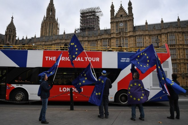 epa06342141 A bus adorned in Union Flag colors passes pro-EU protesters waving European Union flags outside parliament in London,  Britain, 21 November 2017. British Prime Minister Theresa May's senior cabinet members reportedly have agreed that the UK should offer to pay more money to the EU on its departure.  EPA/ANDY RAIN