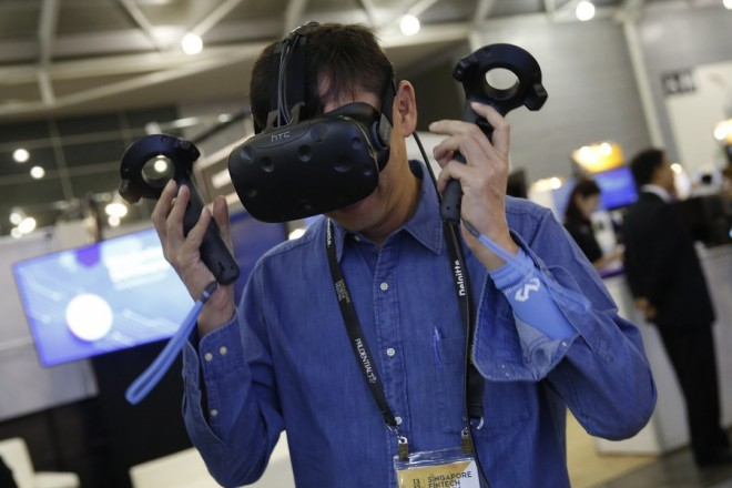 epa06330337 A man tries a virtual reality (VR) headset at a booth during the FinTech Festival in Singapore, 15 November 2017. The second edition of the Fintech Festival, the largest of its kind internationally, brings together 300 exhibitors in the world of FinTech from 13 to 17 November.  EPA/WALLACE WOON