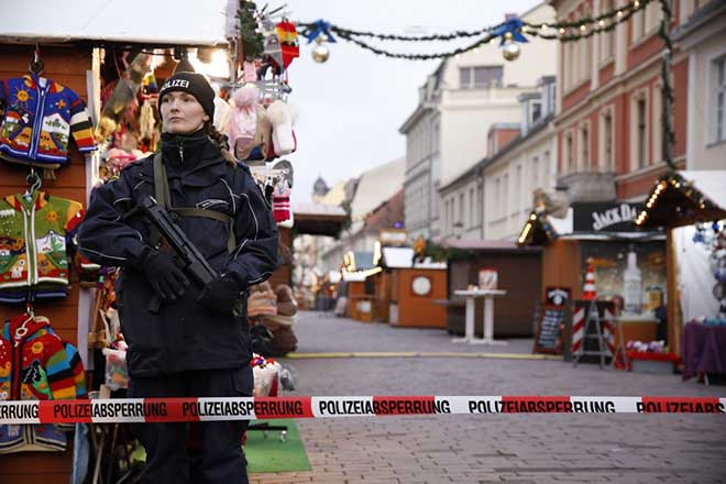 epa06361972 A police officer stands guard behind a police line at the otherwise bustling Potsdam Christmas market, now empty after it was evacuated by police, Potsdam, Germany, 01 December 2017. Police said they had found an explosive device at Potsdam Christmas market, a city near Berlin, and defused it.  EPA/SEBASTIAN GABSCH