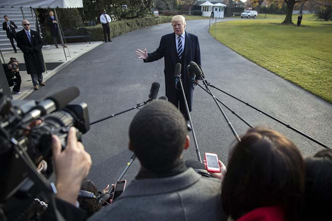 epa06363622 US President Donald J. Trump delivers remarks as he walks to board Marine One on the South Lawn of the White House in Washington DC, USA, 02 December 2017. President Trump commented on the tax reform package passed by the Senate and on the guilty plea by former National Security Advisor Michael Flynn.  EPA/SHAWN THEW