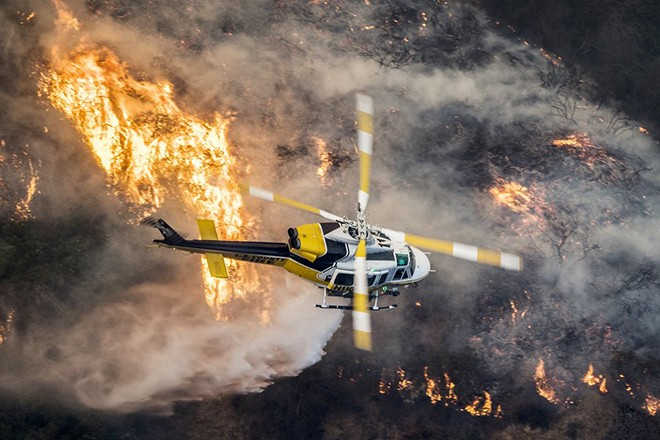 epaselect epa06372496 A Los Angeles County Fire helicopter flies over during the 'Skirball Fire' which began early morning in Bel-Air, California, USA, 06 December 2017. An outbreak of several fires North of Los Angeles has occurred as one of the strongest Santa Ana winds forecast of the season is ongoing and expected to last several days.  EPA/JOHN CETRINO