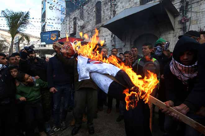epa06373642 Palestinian protestors set fire to a doll of US president Donald J. Trump  during a protest  in the West Bank City of Nablus, 07 December 2017. US president Donald J. Trump on 06 December announced he is recognising Jerusalem as the Israeli capital and will relocate the US embassy from Tel Aviv to Jerusalem.  EPA/ALAA BADARNEH