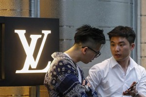 epa06086326 Men stand next to a logo of Louis Vuitton as they wait to enter the store in Singapore, 14 July 2017.  EPA/WALLACE WOON