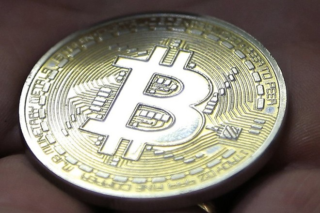 epa06382936 (FILE) - A visitor holds a Bitcoin (virtual currency) souvenir coin, during a webinar by Russian businessman, Orthodox activist and founder the Crypto exchange CryptoSterlingClub Alisa, German Sterligov at the main office of CryptoSterlingClub Alisa in Moscow, Russia, 29 August 2017 (reissued 11 December 2017). Reports on 11 December 2017 state Cboe Global Markets that late 10 December 2017 launched Bitcoin futures, also called derivates, saw the futures soar more than 20 per cent following their debut on 11 December. The rapid rise of more than 20 per cent twice forced a halt to trading on Bitcoin futures..  EPA/MAXIM SHIPENKOV