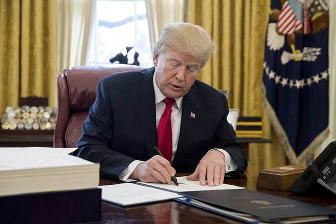 epa06403233 US President Donald J. Trump signs bills in the Oval Office of the White House in Washington, DC, USA, 22 December 2017. Trump signed the tax bill, a continuing resolution to fund the government, and a missile defense bill before leaving to spend Christmas in Mar-a-Lago, Florida.  EPA/MICHAEL REYNOLDS