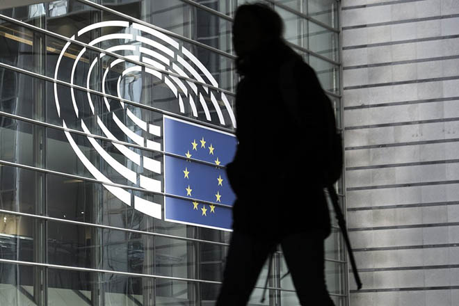 epa06418376 A man walks in front of the European Parliament building with the logo of the parliament, in Brussels, Belgium, 05 January 2018.  EPA/OLIVIER HOSLET