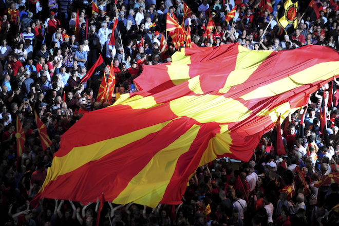 epa04755869 Supporters of the ruling VMRO DPMNE party carry a large Macedonian flag during a rally in support for the government, in Skopje, The Former Yugoslav Republic of Macedonia on 18 May 2015. After the big opposition meeting a day earlier in Skopje when opposition members asked for resignation of the government, the ruling VMRO DPMNE party organized a counter-protest to support the government and Prime Minister Nikola Gruevski. Tens of thousands people attended the rally.  EPA/GEORGI LICOVSKI