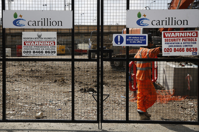 Company logos sit on the gates of a construction site for new apartment blocks built by Carillion Plc in the Canning Town district of London, U.K., on Friday, July 25, 2014. Balfour Beatty, the U.K. construction company whose chief quit in May after predicting a profit drop, is in merger talks with rival Carillion to form the country's biggest builder with a market valuation of about 3 billion pounds ($5 billion). Photographer: Simon Dawson/Bloomberg