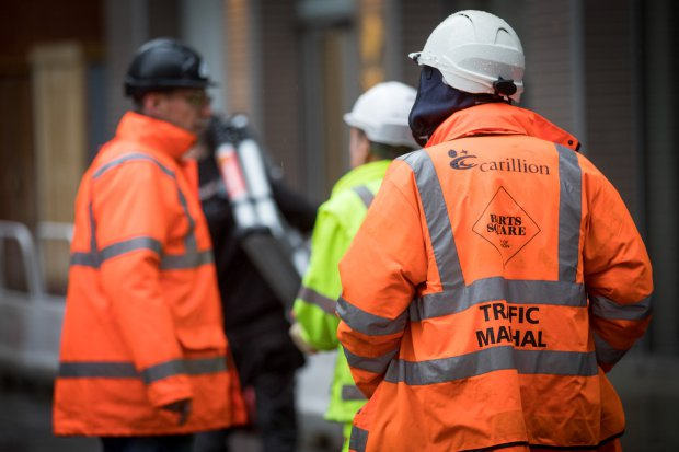 A member of Carillion's staff directs traffic as subcontractors collect their tools on the Barts Square development, operated by Carillion Plc, in London, U.K., on Monday, Jan. 15, 2018. Carillion, a U.K. construction company with government contracts in everything from hospitals to the HS2 high-speed rail project, filed for compulsory liquidation after failing in a last-ditch effort to shore up finances and get a government bailout. Photographer: Jason Alden/Bloomberg via Getty Images