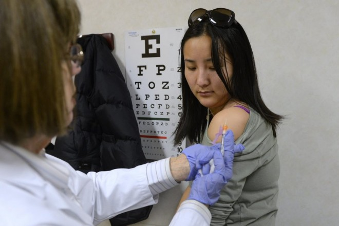 epa03530556 Lu Ji (R) receives an injection of an influenza virus vaccine called 'afluria', administered by a doctor at a medical clinic in Alexandria, Virginia, USA, 10 January 2013. The United States is experiencing one of the worst flu seasons in a decade, according to reports, which has resulted in a spiked increase of demand for flu vaccines.  EPA/MICHAEL REYNOLDS
