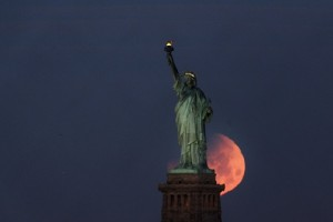 epa06487897 The moon sets behind the Statue of Liberty in New York, New York, USA, 31 January 2018. The moon is a supermoon, blue moon and total lunar eclipse that NASA has dubbed a 'Super Blue Blood Moon'. This is the last one in a series of three consecutive 'Supermoons', dubbed the 'Supermoon Trilogy'.  The previous 'Supermoons' appeared on 03 December 2017 and on 01 January 2018. A 'Supermoon' commonly is described as a full moon at its closest distance to the earth with the moon appearing larger and brighter than usual.  EPA/JUSTIN LANE