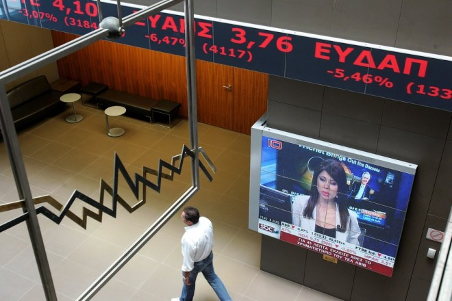 epa02859744 A man walks past an electronic board recording the up and downs of a session at the Stock Exchange in Athens, Greece, 08 August 2011. Shares on the Athens Stock Exchange are tumbling, with the general price index down 4.75 percent, reaching 1,011.60 points.  EPA/SIMELA PANTZARTZI
