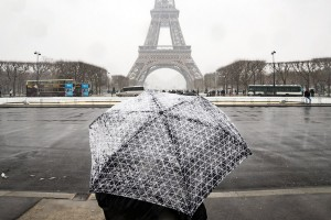 epa06500703 A tourist takes pictures of the Eiffel tower during a snow episode in Paris, France, 06 February 2018. Temperatures dropped with snow flurries around the capital.  EPA/ETIENNE LAURENT
