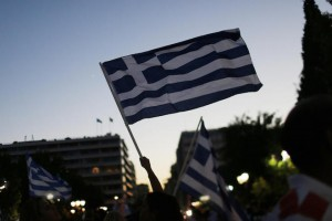 "Supporters of the No vote wave Greek flags after the first results of the referendum at Syntagma square in Athens, Sunday, July 5, 2015. Greece faced an uncharted future as officials counted the results of a referendum Sunday on whether to accept creditors' demands for more austerity in exchange for rescue loans, with three opinion polls showing a tight race with a narrow victory likely for the ""no"" side. (AP Photo/Emilio Morenatti)"