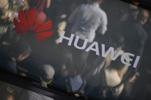 epa06269535 Visitors are reflected in a window with the Huawei company logo during the official launch event for the Huawei Mate 10 smartphone series in Munich, southern Germany, 16 October 2017. The chinese manufacturer's new offering is aimed at the luxury market.  EPA/PHILIPP GUELLAND