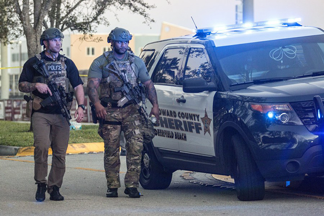 epa06525856 Two SWAT officers walk in front of the side entrance of the Marjory Stoneman Douglas High School after a shooting in Parkland, Florida, USA, 14 February 2018. Multiple fatalities have been reported and several more injured at a high school northwest of Miami. According to law enforcement the suspect is in custody. Some media are reporting the suspect as former student, Nicolas Cruz.  EPA/CRISTOBAL HERRERA