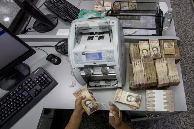 epa05677470 A bank worker counts 100 Bolivares bills in Caracas, Venezuela, 15 December 2016. Thousands of Venezuelans head to the banks to get rid of their 100 Bolivares bills, the highest denomination of the country's currency, which will be withdrawn from circulation on 15 December by order of Venezuelan President Nicolas Maduro.  EPA/MIGUEL GUTIERREZ